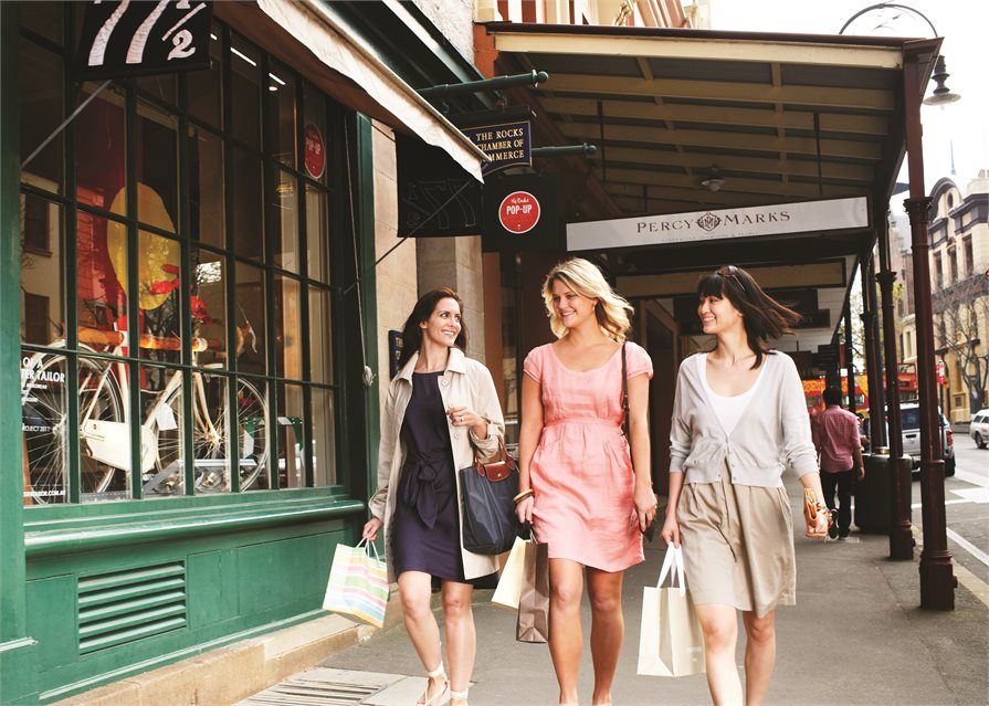 Three women walking along past shops in Sydney