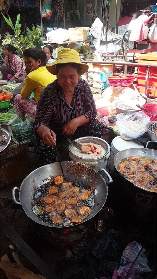 Local woman cooks traditional street food in Phnom Penh