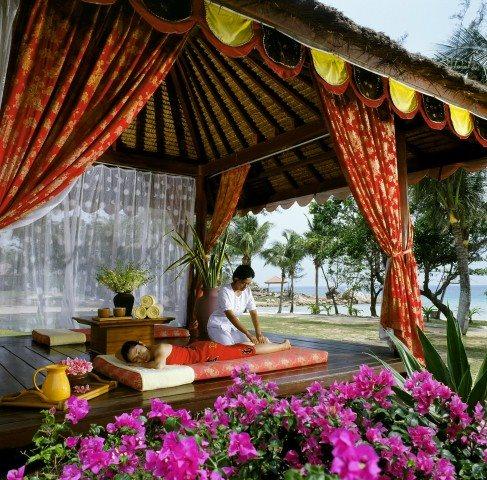 Woman receiving a Balinese massage on the beach