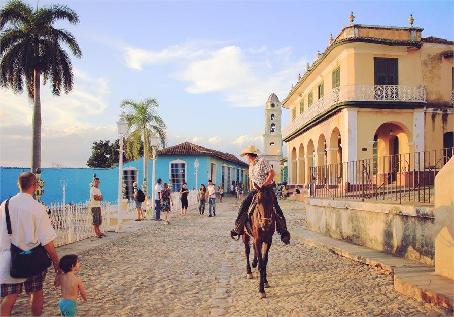 Cuban street man riding donkey old buildings