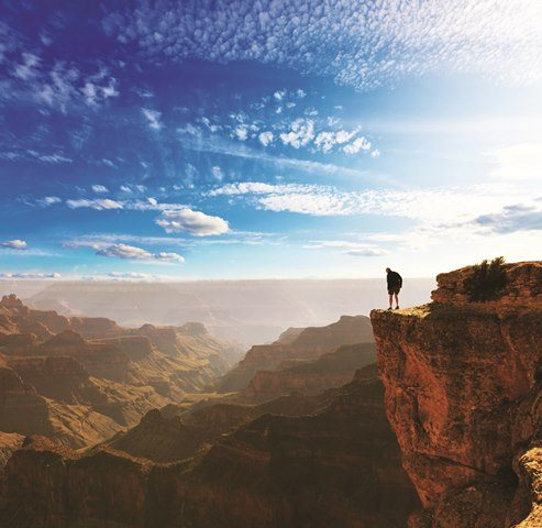 Man looking over the cliff in the Grand Canyon