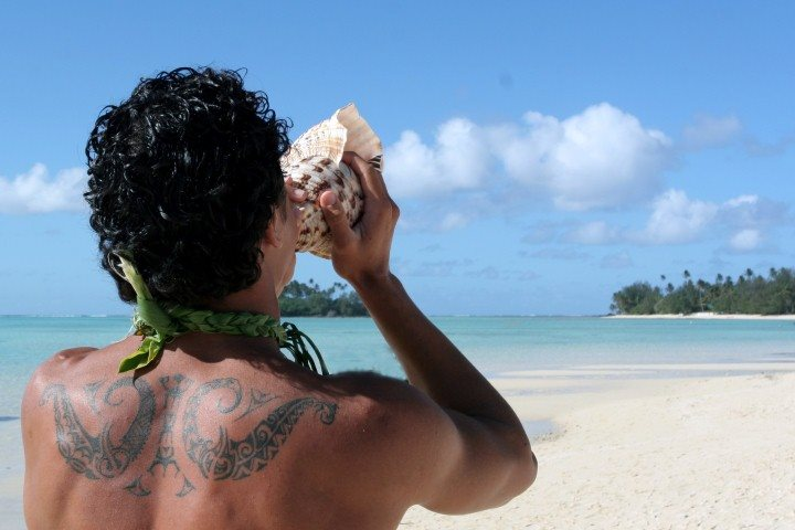 Cook Island man blowing a shell horn on the beach