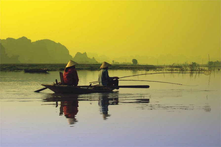 Fishermen on boat in Vietnam with Sun rise